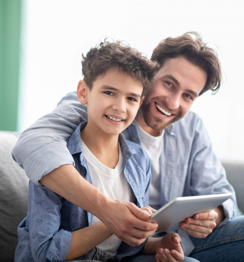 family-time-happy-dad-and-son-using-digital-tablet-browsing-internet-online-at-home-sitting-e1632233068896.jpg